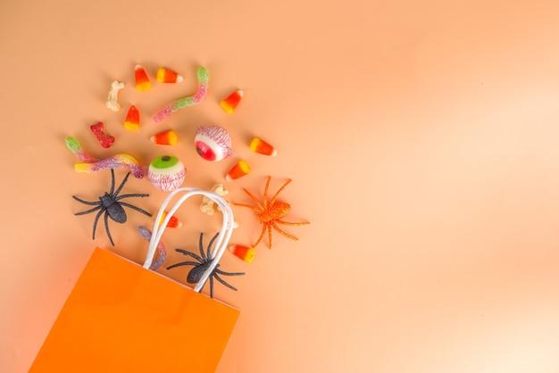 해피 할로윈 날 휴일 배경입니다. 어린이 파티를 위한 과자와 장식이 있는 평평한 평지, 거미가 든 버킷 팩, 사탕 과자, 박쥐, 화려한 주황색 종이 복사 공간 위쪽 전망