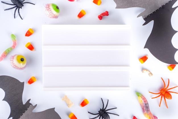 해피 할로윈 날 휴일 배경입니다. 어린이 파티를 위한 과자와 장식이 있는 평평한 평지, 거미가 있는 버킷 팩, 사탕 과자, 박쥐, 흰색 테이블 복사 공간 상단 보기 프레임
