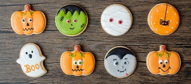 Счастливый день хэллоуина с забавными печеньями, установленными на фоне деревянного стола. уловка или угроза, привет, октябрь, осенняя осень, концепция праздника, вечеринки и праздника