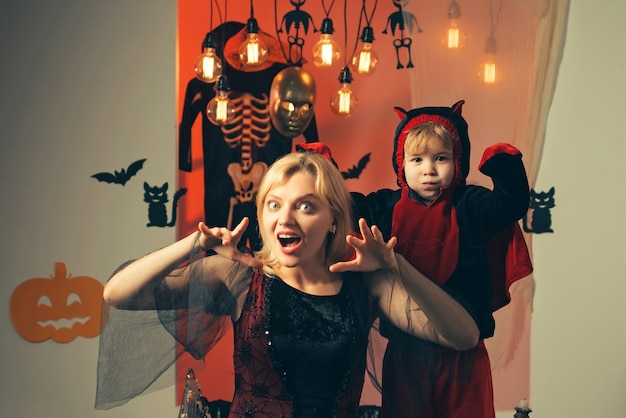 Happy halloween family with pumpkins on a halloween background. halloween dresses on mother and son
