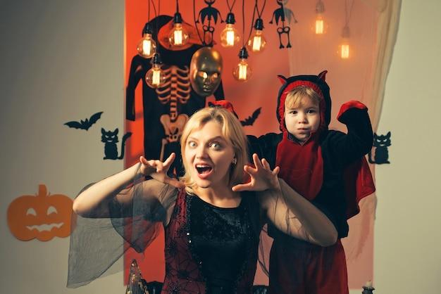 Счастливая семья хэллоуина с тыквами на фоне хэллоуина. хеллоуин платья на мать и сына