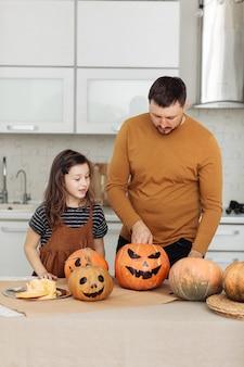 해피 할로윈. 아버지와 어린 딸이 호박을 조각합니다. 행복한 가족이 할로윈을 준비하고 있습니다.