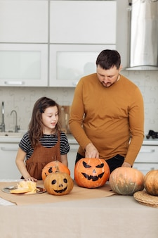 Happy halloween. father and little daughter carve a pumpkin. happy family is preparing for halloween.