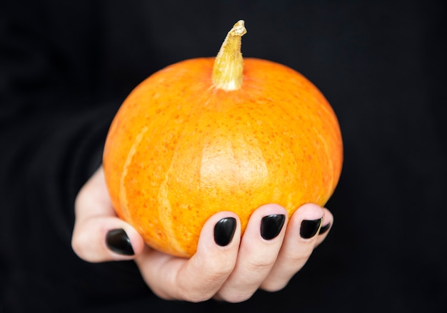 Happy halloween.  female hands holding funny pumpkins on black background. manicure with black nail polish Premium Photo