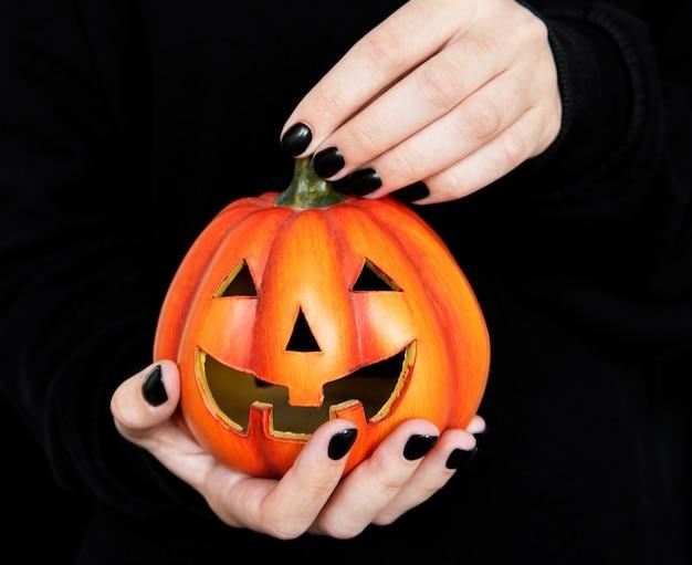 Happy halloween  female hands holding funny pumpkins on black background