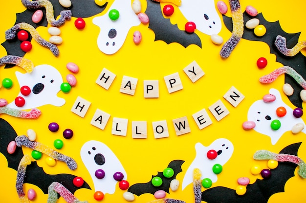 Happy halloween and frame made of paper homemade bats and paper ghosts and multicolored candies and worms from gummy on a bright yellow background