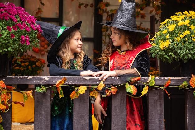 魔女の衣装を着た幸せなハロウィーンの女の子は家の近くの秋に楽しんでいます