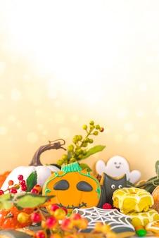 ハッピーハロウィングリーティングカードの背景。トリックオアトリートのコンセプト。伝統的なジンジャーブレッドクッキー、キャンディー、お菓子、カボチャ、ボケライト効果のある装飾