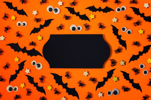 Happy halloween greeting card with small decorative bats, spiders and puppet eyes.