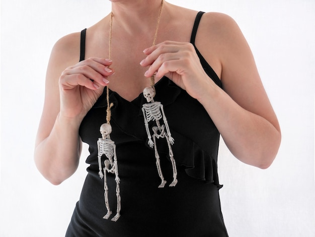 Happy halloween the hands of woman in black dress holding two skeletons hanging on the gallows