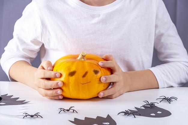 Счастливого хэллоуина. красивый маленький мальчик, держащий тыкву с забавным лицом.