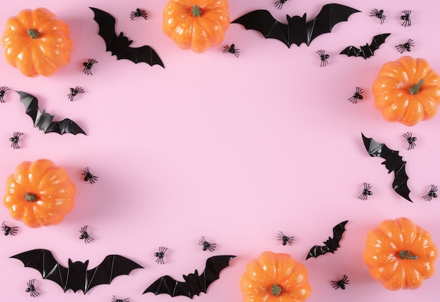 Happy halloween holiday background with trick or treat, pumpkins, candy and spiders on pastel pink background.