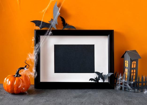 Счастливого праздника хэллоуина. черная рамка на оранжевом фоне. хэллоуинские украшения, тыквы, летучие мыши, черная рамка.