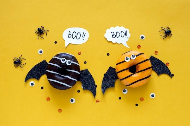 幸せなハロウィーンの休日のコンセプトです。子供のための面白い食べ物-黒のクモと目でバットコスチュームとして明るい黄色の背景に怖いドーナツ。ハロウィーンパーティーのグリーティングカード。スペルワードブー