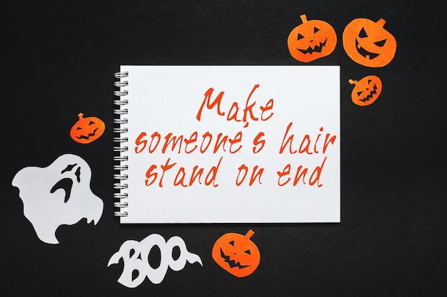 Happy halloween holiday concept. notepad with text make someone hair stand on end on black background with bats, pumpkins and ghosts