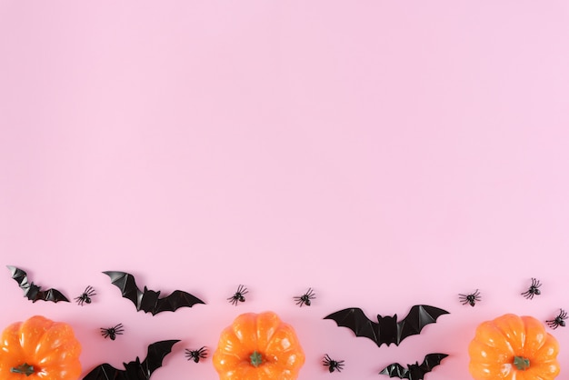 Happy halloween holiday  with trick or treat, pumpkins, candy and spiders on pastel pink background.