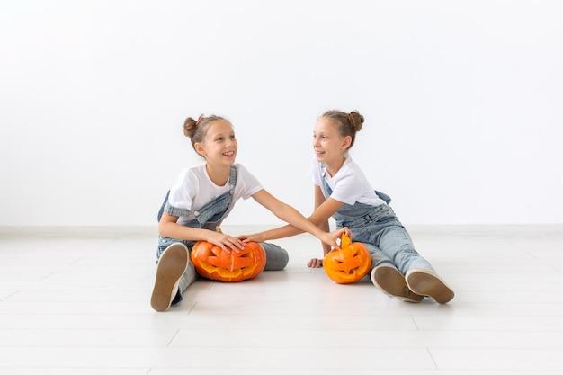 해피 할로윈, 휴일, 어린 시절 개념 - 호박 잭-오-랜턴을 들고 실내에서 시간을 보내는 동안 즐거운 시간을 보내는 귀여운 쌍둥이 자매