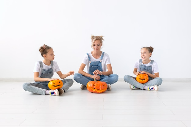 Happy halloween and holidays concept - a mother and her daughters with pumpkins. happy family preparing for halloween.
