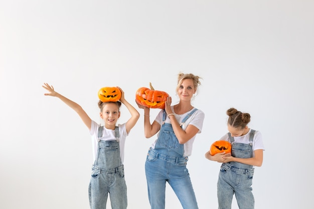 Happy halloween and holidays concept - a mother and her daughters with pumpkins. happy family