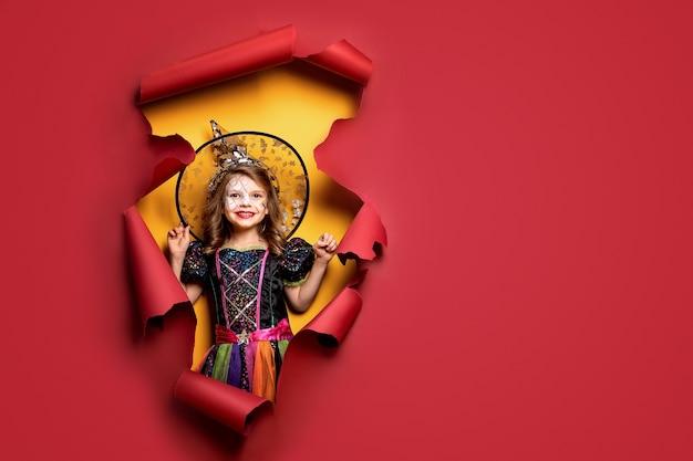 Счастливого хэллоуина. смеющаяся смешная девочка в костюме ведьмы на хэллоуин смотрит, улыбается и пугает сквозь дыру красного цвета