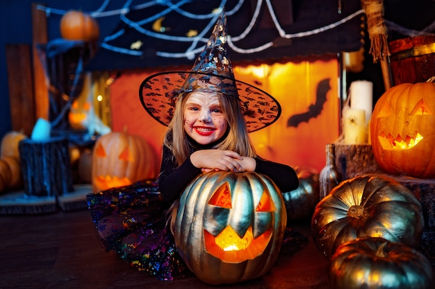 Happy halloween. a little beautiful girl in a witch costume celebrates with pumpkins