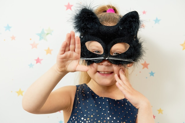 Happy halloween . little girl child in black cat mask, carnival costume. funny face