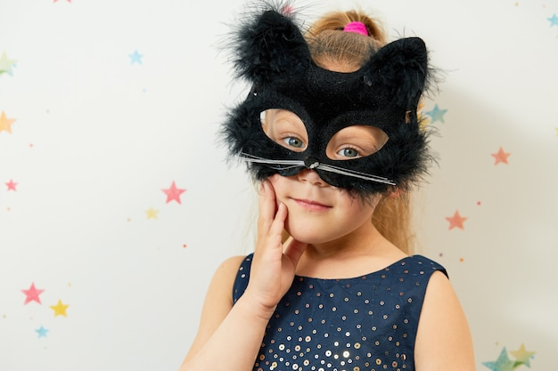 ハッピーハロウィン。黒い猫のマスク、カーニバルの衣装の小さな女児。変な顔