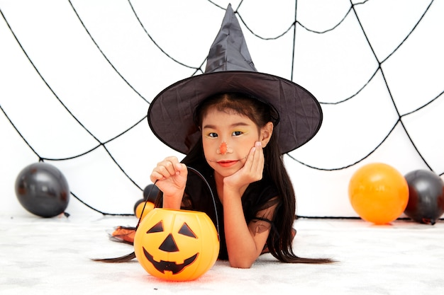 Happy halloween little witch with a pumpkin