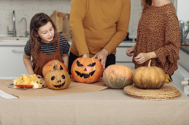 해피 할로윈. 어머니, 아버지와 딸이 호박을 조각합니다. 행복한 가족이 할로윈을 준비하고 있습니다.