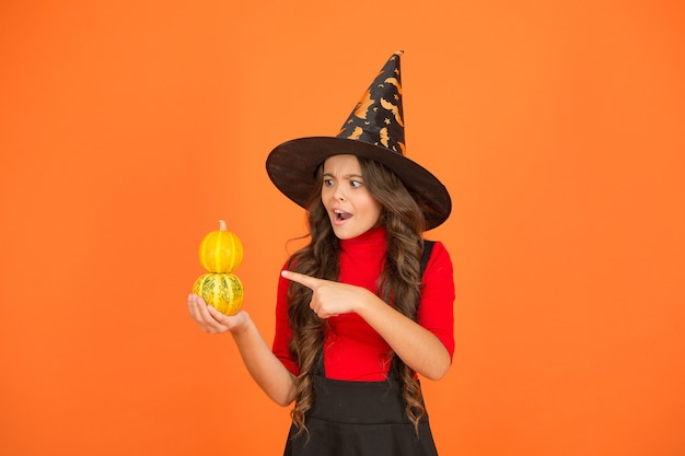 Happy halloween party kid wearing witch cosplay costume and having fun while celebrating autumn traditional holiday pointing finger on pumpkin, halloween jack o lantern.