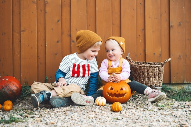 Счастливого хэллоуина! фото осеннего настроения со стильной девушкой и мальчиком, весело проводящими время в сельской местности. детская вечеринка и концепция празднования. прелестные маленькие дети с тыквами на деревянном фоне амбара снаружи.