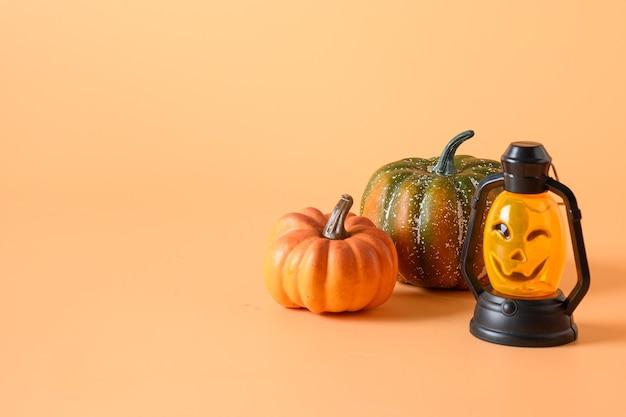 Счастливого хэллоуина. тыквенная голова джек-о-фонарь и тыквы на оранжевом бумажном фоне