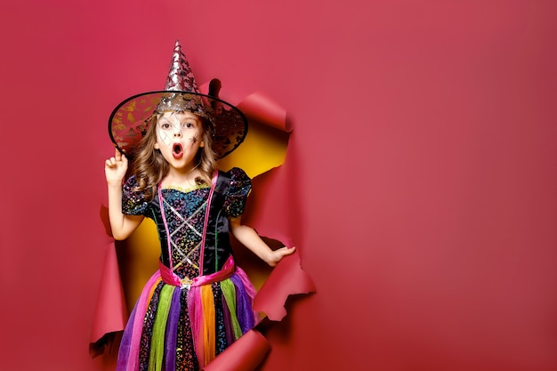 Счастливого хэллоуина. удивленная смешная детская девочка в костюме ведьмы на хэллоуин, просматривающая дыру на красном, желтом бумажном фоне. copyspace