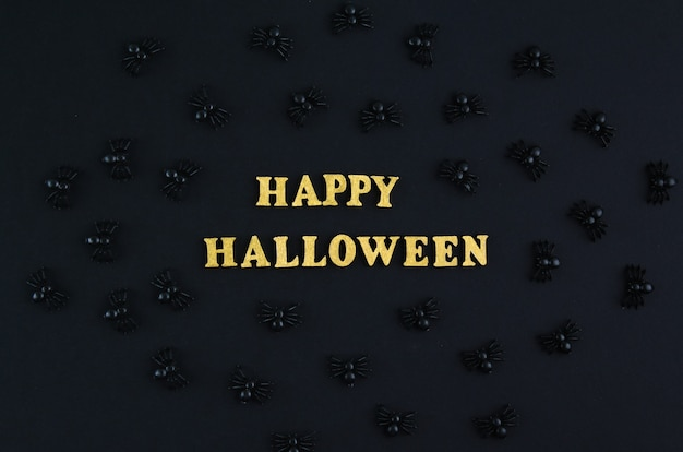 Happy halloween text holiday concept. black spiders over black background.