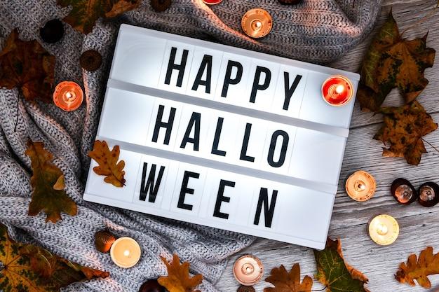 Счастливого хэллоуина. текст в белом световом поле, на фоне свитера, сушеные листья хэллоуин осенние украшения. призрак, тыква, летучая мышь, черный кот. украшение дома. вид сверху. боке свет