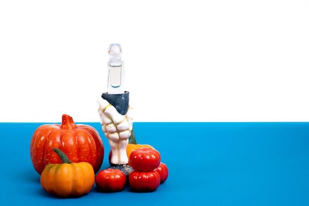 Счастливого хэллоуина. рука ведьмы с зельем и много разных тыкв на бело-синем фоне
