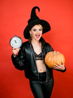 Happy halloween young women in black witch halloween costumes on party over red background funny fac...