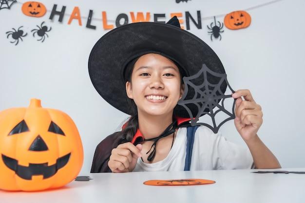 Азиатская девушка ведьма костюм играет в комнате happy halloween