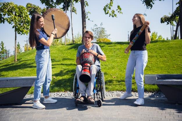 야외에서 라이브 악기 음악을 연주하는 친구와 함께 시간을 보내는 휠체어에 행복 한 장애인 남자.
