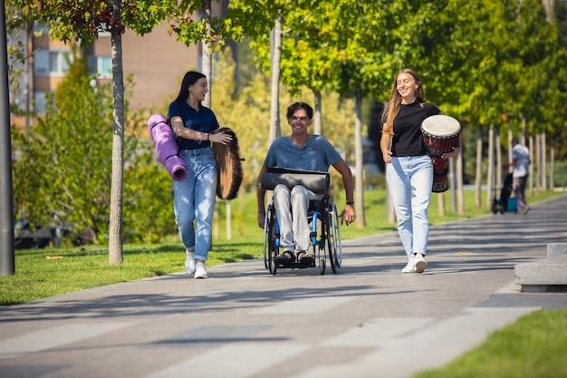 車椅子の幸せな障害者が屋外で楽器の生演奏をしている友達と時間を過ごしています。