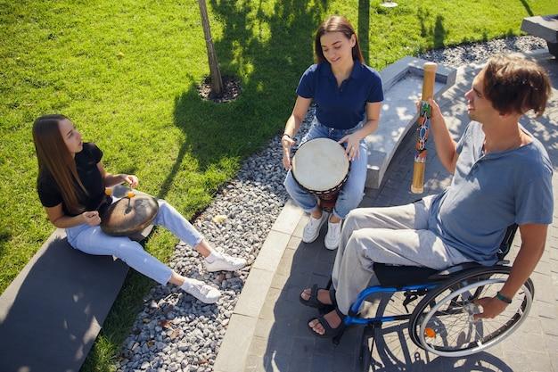 Felice handicappato uomo su una sedia a rotelle di trascorrere del tempo con gli amici che suonano musica strumentale dal vivo all'aperto.