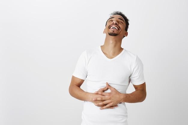 Счастливый красивый афро-американский парень смеется, хихикает и трогает живот