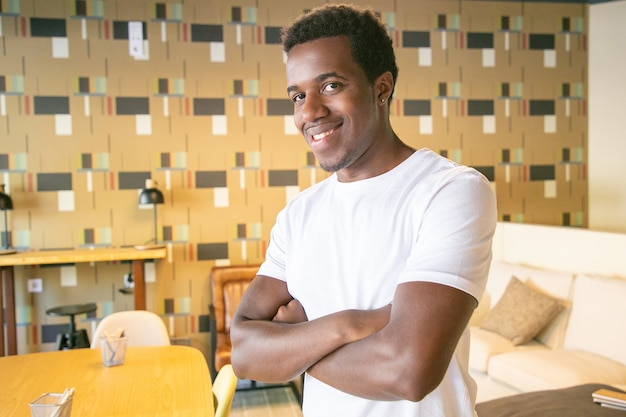 Счастливый красивый афро-американский парень позирует со скрещенными руками в коворкинге или интерьере кафе, глядя в камеру и улыбаясь