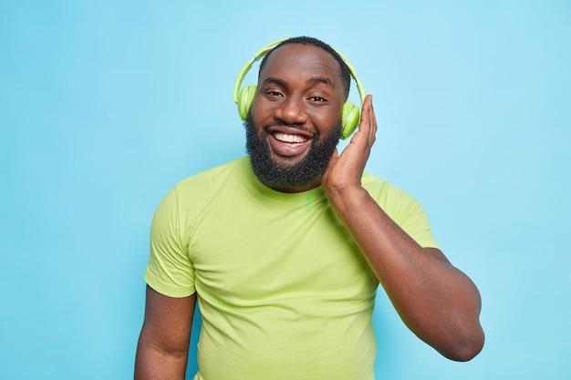 두꺼운 수염을 기른 행복한 미남 아프리카계 미국인 남성은 스테레오 헤드폰을 끼고 완벽한 사운드를 즐깁니다. 파란 벽에 격리된 캐주얼한 녹색 티셔츠를 입고 있습니다.