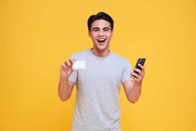 노란색에 손에 신용 카드와 스마트 폰을 보여주는 행복 잘 생긴 아시아 남자.