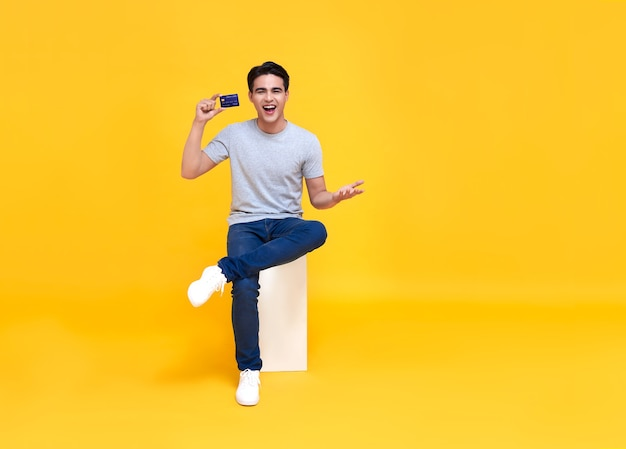 Happy handsome asian man showing credit card in hand isolated on yellow background.
