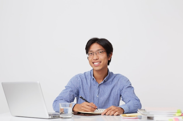 Happy handsome asian young business man in glasses writing in notebook working with laptop  over white wall