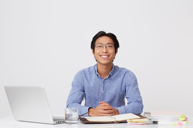 Happy handsome asian young businessman in glasses in blue shirt sitting at the table with laptop over white wall