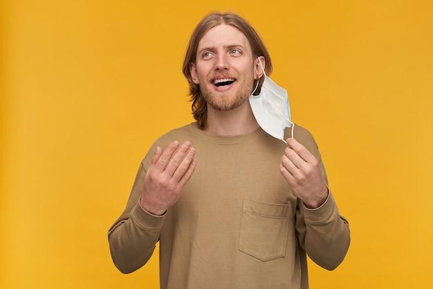 Счастливый, красивый бородатый парень со светлой прической. в бежевом свитере. снимает медицинскую маску с лица. дышать свежим воздухом. наблюдая слева за копией пространства, изолированной над желтой стеной