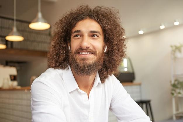 Felice bel ragazzo barbuto con riccioli che guarda da parte e sorride ampiamente, essere di buon umore, incontrare gli amici durante la pausa pranzo, posare sulla caffetteria